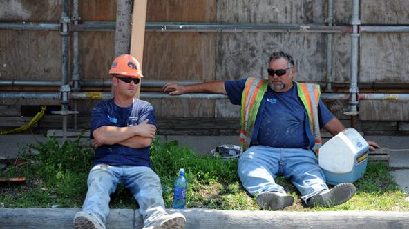 RAM Conrtuction Services workers Kevin Hamm, Howell, and Joseph Zucca, Westland, rest in the shade during their lunch break on Wednesday. Zucca attempts to stay cool by drinking lots of fluids. Melanie Maxwell I AnnArbor.com
