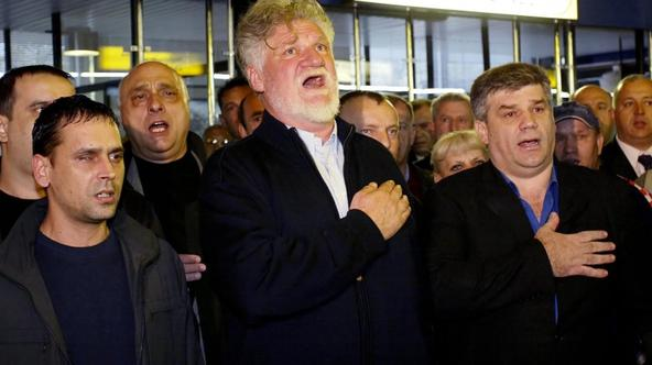'Retired Croatian General Slobodan Praljak (C) sings the national anthem at Zagreb airport 05 April 2004 before leaving for the UN war crimes tribunal in the Hague. Six former Bosnian Croat officials