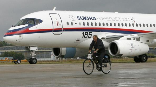 'A cyclist rides past a Sukhoi Superjet 100, an airplane-participant of the MAKS-2009 international air show, in Zhukovsky, outside Moscow, August 14, 2009. The annual air show, a marketplace for airl