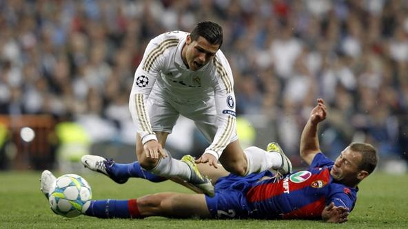 'Real Madrid\'s Cristiano Ronaldo (L) is tackled by CSKA Moscow\'s Vasili Berezutski during their Champions League round of 16 second leg soccer match at Santiago Bernabeu stadium in Madrid March 14,