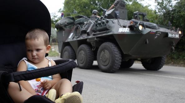 'A Kosovo Serb child sits in a pram as Slovenia\'s KFOR vehicle passes by in the village of Rudare near the town of Zvecan August 2, 2011. The NATO force in Kosovo said on Tuesday it had requested add