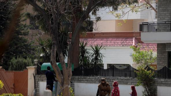 \'Pedestrians walk past a house where family members of slain Al-Qaeda leader Osama bin Laden are believed be be held, in Islamabad on March 17, 2012. A Pakistan court March 17 remanded family members
