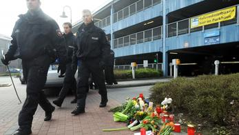 'Policemen walk past candles and flowers laid down on March 26, 2012 in front of a parking deck in Emden, western Germany, where an eleven-year old girl was found dead. Police said that they were sear
