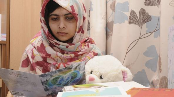 'Pakistani schoolgirl Malala Yousufzai reads a card as she recuperates at the The Queen Elizabeth Hospital in Birmingham, in this undated handout photograph released to Reuters on November 8, 2012. Ma