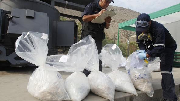 'Anti-narcotics workers display bags containing cocaine in front of an incinerator in Lima April 26, 2012. More than four tonnes of drugs, which includes cocaine, cocaine paste and marijuana, that wer